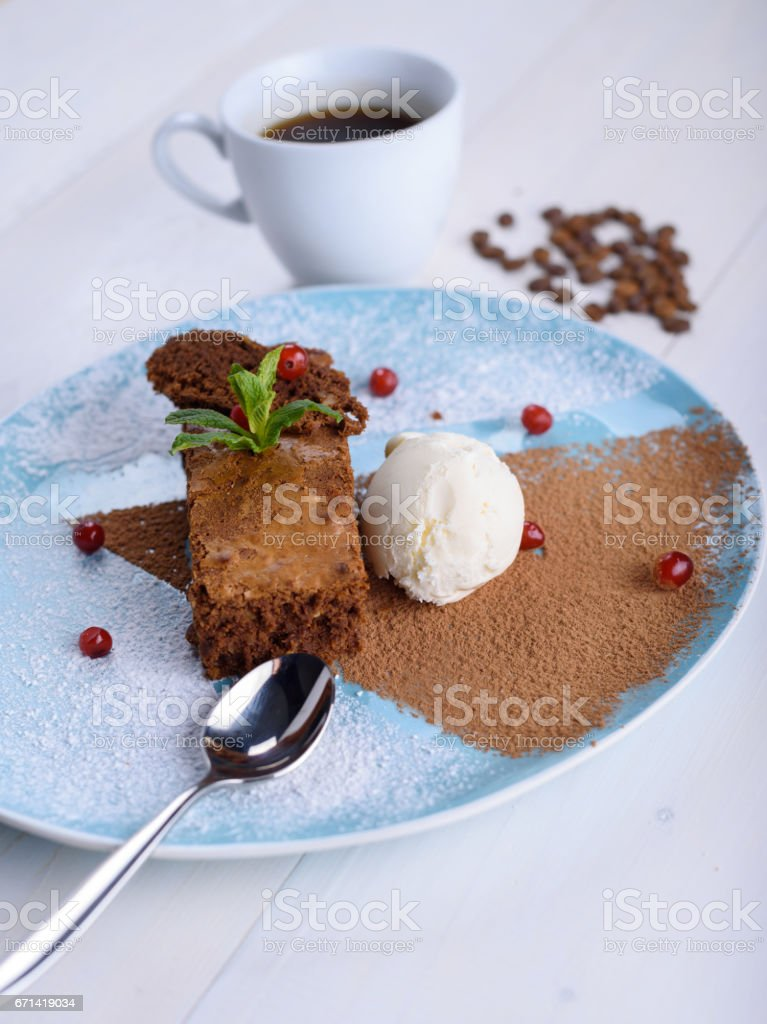 Chocolate brownie with ice cream on a blue plate next to a cup of coffee. Chocolate cake with coffee stock photo