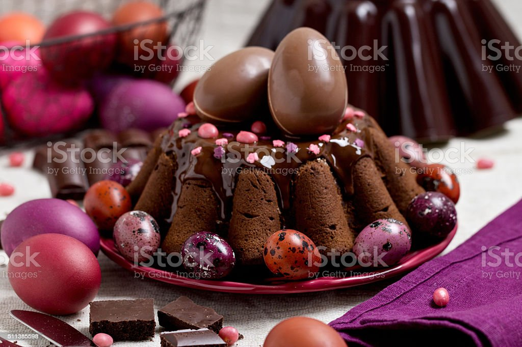 Chocolate cake and Easter eggs colored in purple and brown. stock photo