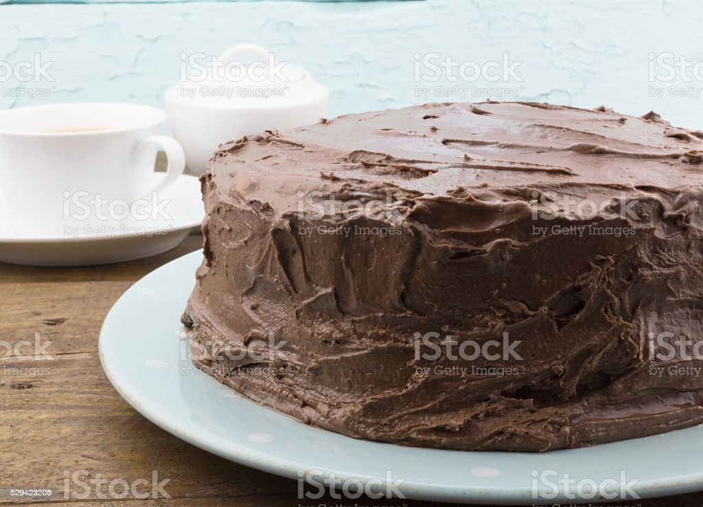 Chocolate cake close up on blue plate on rustic wood stock photo