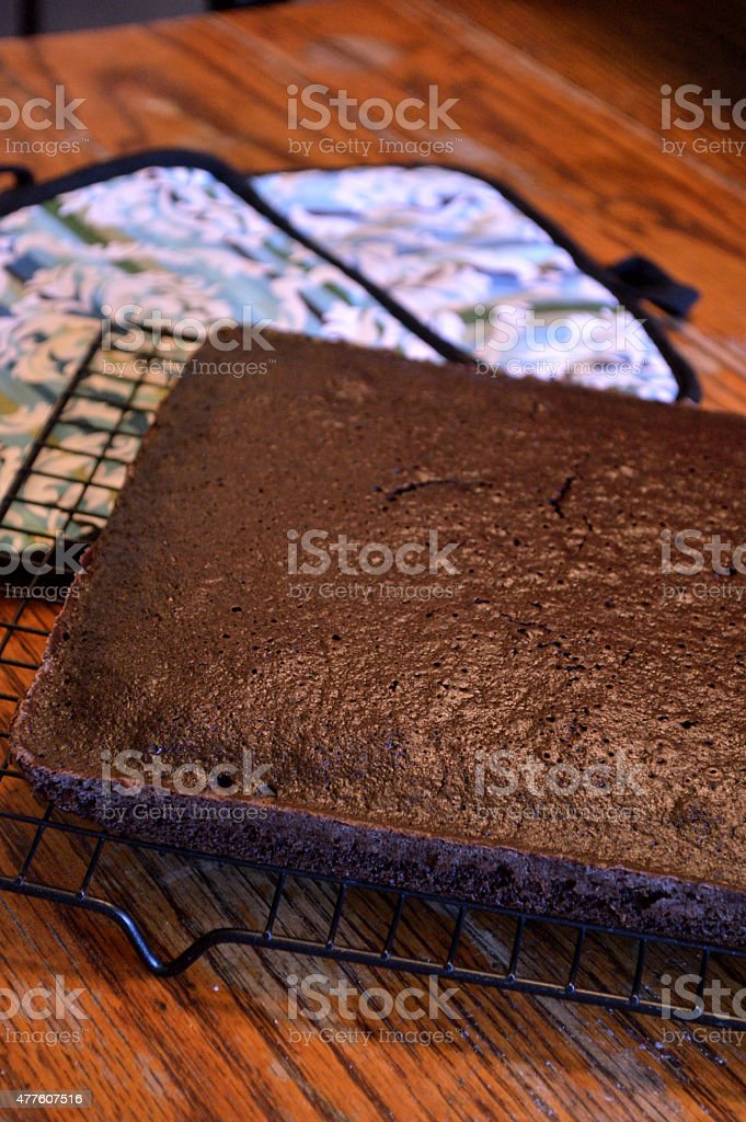Chocolate cake cooling on rack on wooden table stock photo