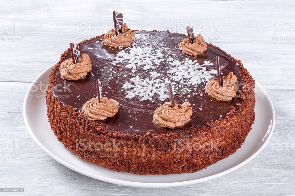 chocolate cake decorated with chocolate chips and icing-sugar snowflake, close-up stock photo