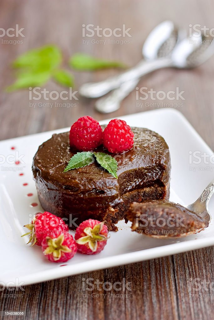 Chocolate cake dessert with berries and spoon on plate stock photo