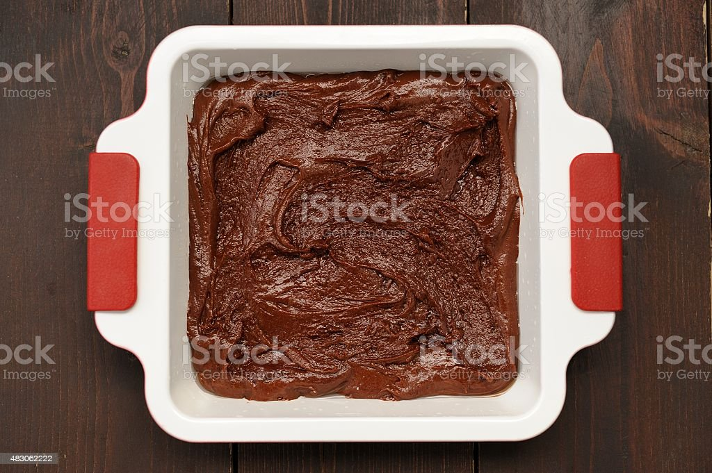 Chocolate cake in square baking dish on wooden background stock photo