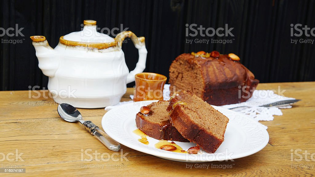 chocolate cake with almonds, candied lemon and teapot stock photo