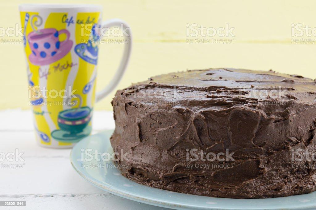 Chocolate cake with coffee mug against yellow background stock photo