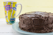 Chocolate cake with coffee mug against yellow background