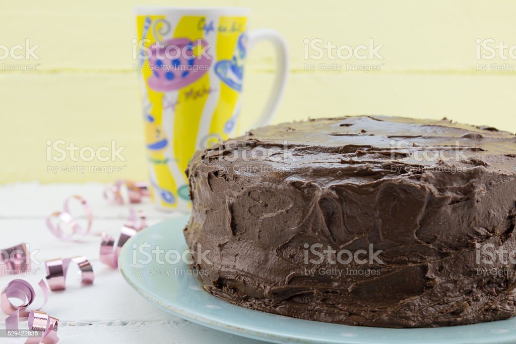 Chocolate cake with festive coffee mug and ribbons in background stock photo