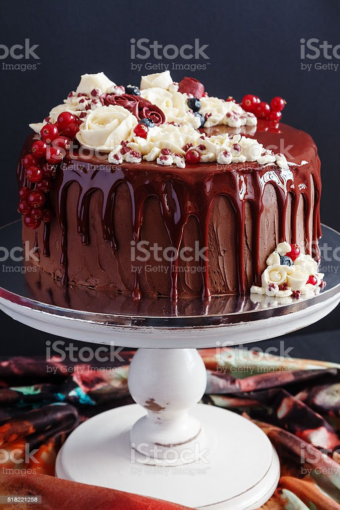 Chocolate cake with glaze and buttercream flowers stock photo