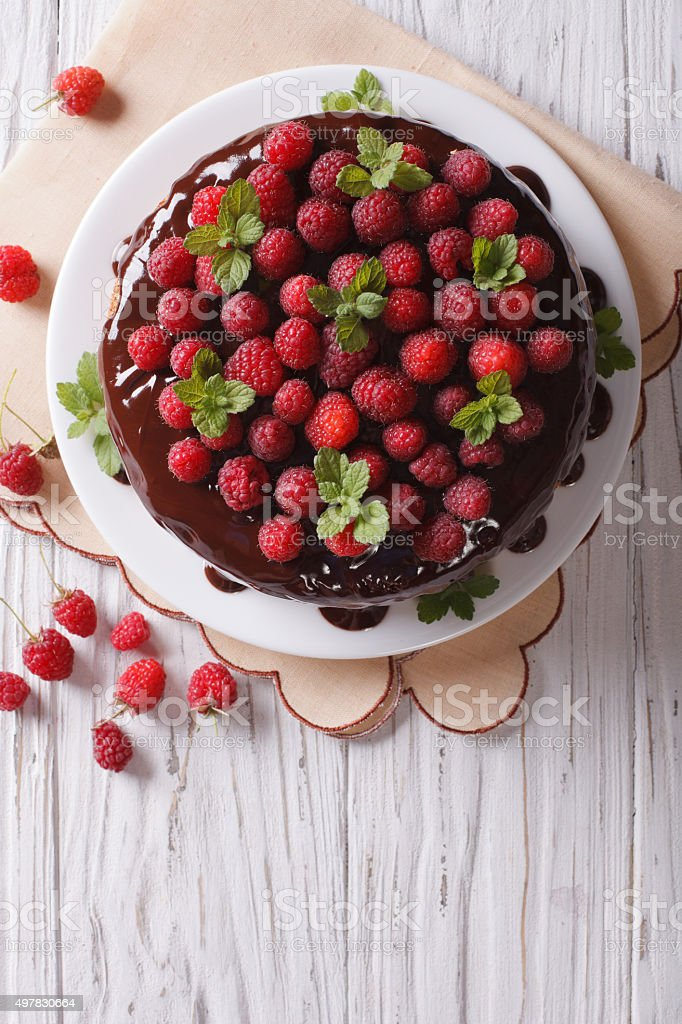 Chocolate cake with raspberries and mint vertical top view stock photo