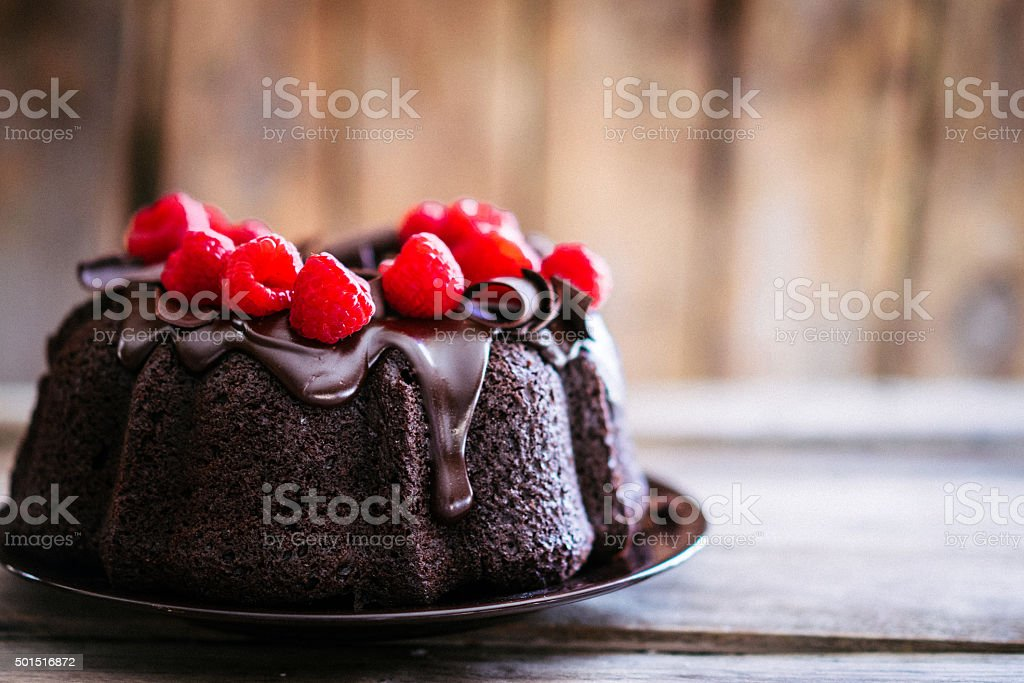 Chocolate cake with raspberries on rustic wooden background stock photo