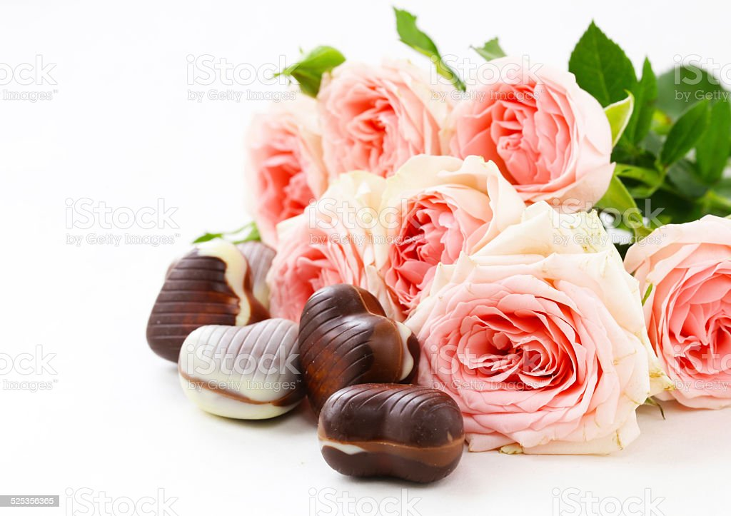 chocolate candy in the shape of hearts and pink roses stock photo