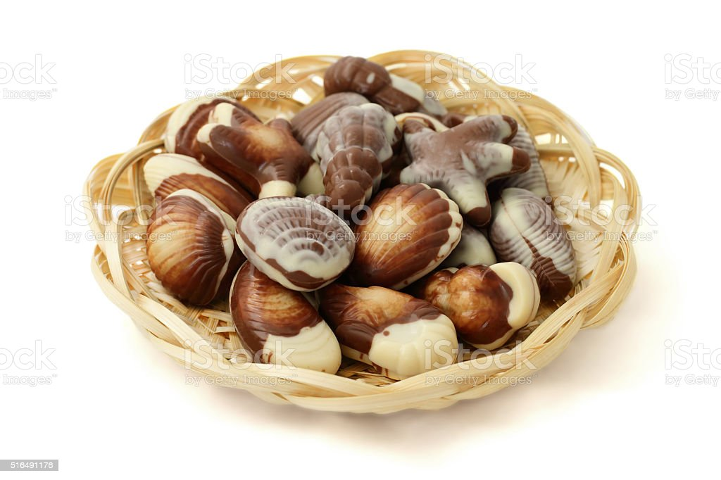 chocolate candy shaped sea shells in a wicker basket stock photo
