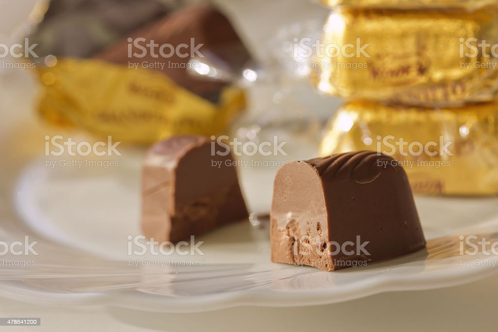 Chocolate candy,cut in half, on the plate.Closeup stock photo