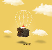 Chocolate cherry cake with parachute on yellow sky without text
