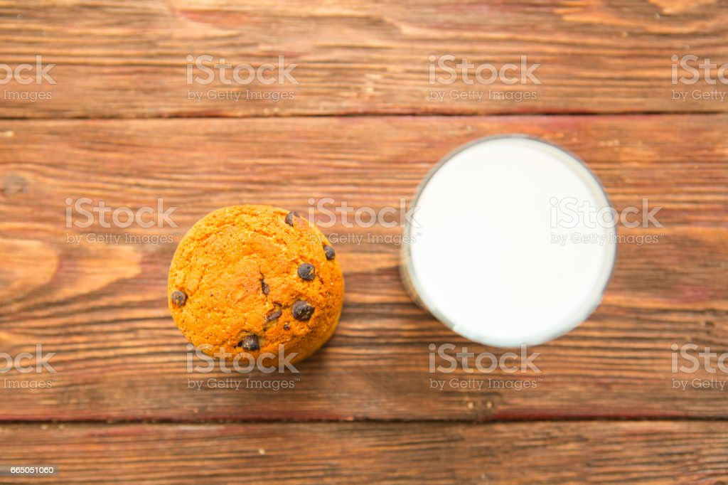 Chocolate chip cookies and glass of milk on wooden table stock photo
