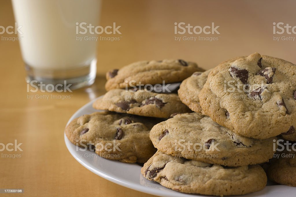 Chocolate Chip Cookies Plate and Glass of Milk on Table royalty-free stock photo