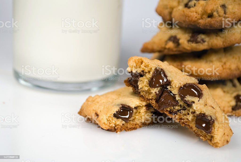 chocolate chip cookies with glass of milk in background stock photo