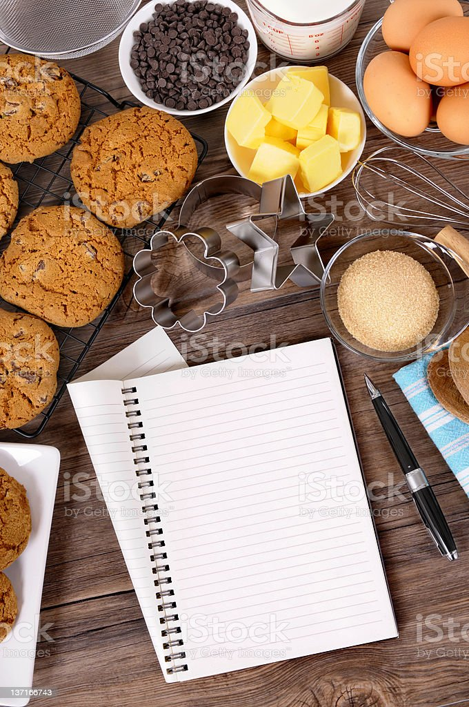Chocolate chip cookies with ingredients and notebook royalty-free stock photo
