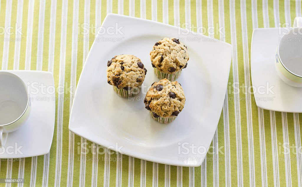 Chocolate chip muffins on white plate and green striped tablecloth royalty-free stock photo