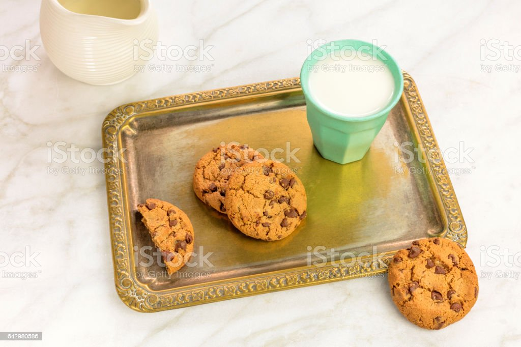 Chocolate chips cookies and milk on vintage tray stock photo