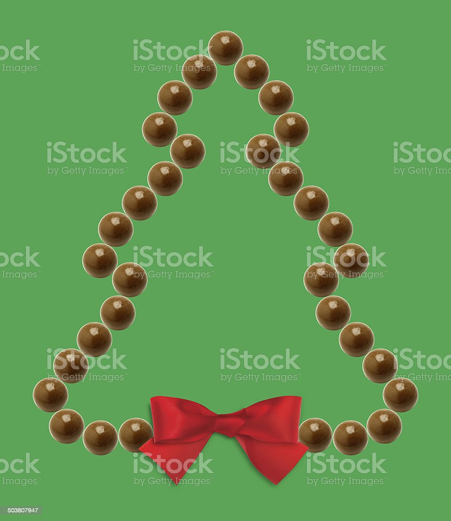 Chocolate Christmas tree with red ribbon on green background stock photo