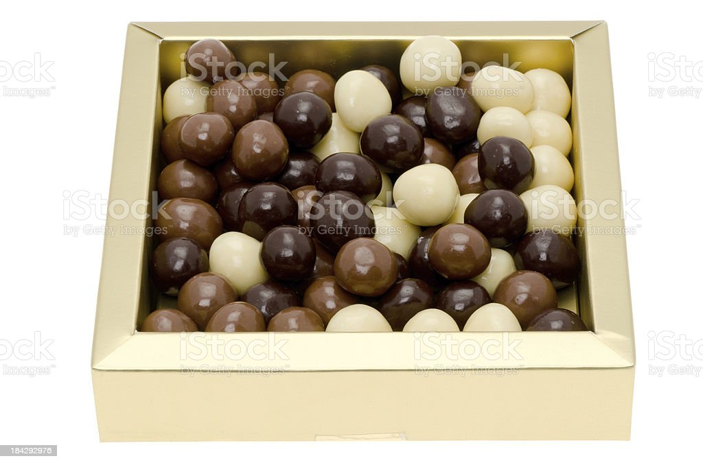 Chocolate coated hazelnuts in a gold box royalty-free stock photo