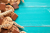 Chocolate cookies and wheat on old turquoise table