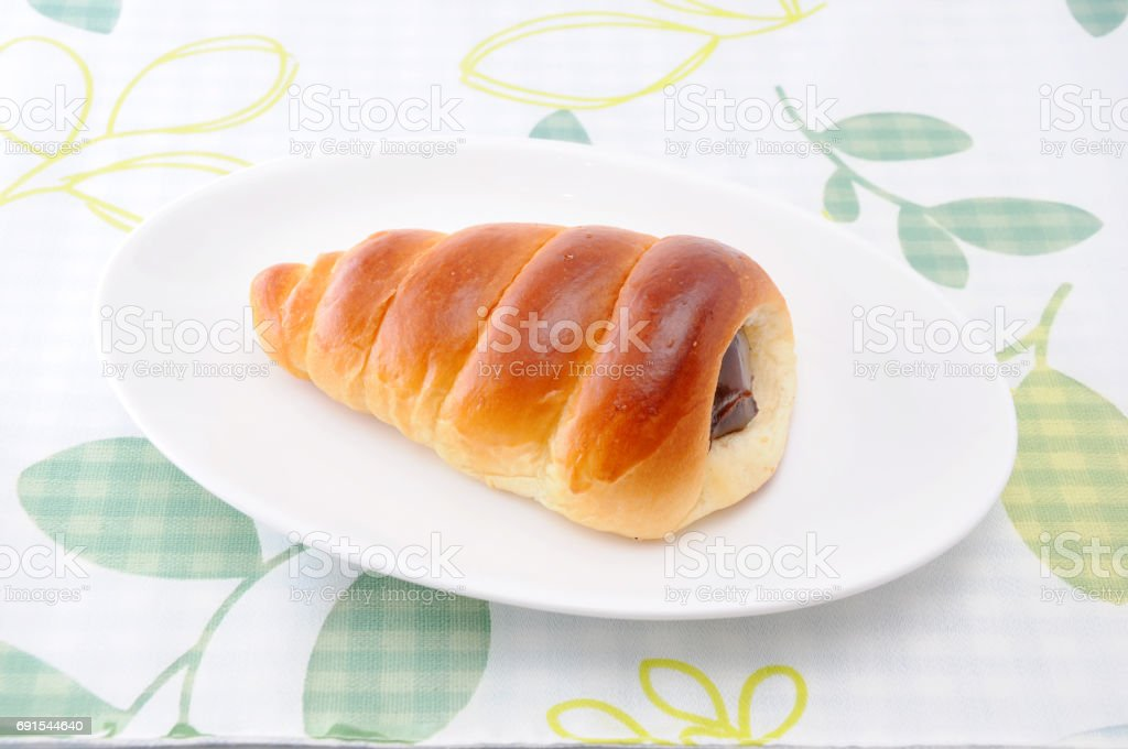 chocolate cornet butter bread roll on a plate on table stock photo