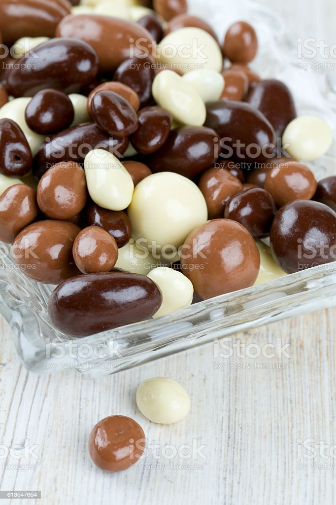 chocolate covered nuts and raisins on wooden surface stock photo