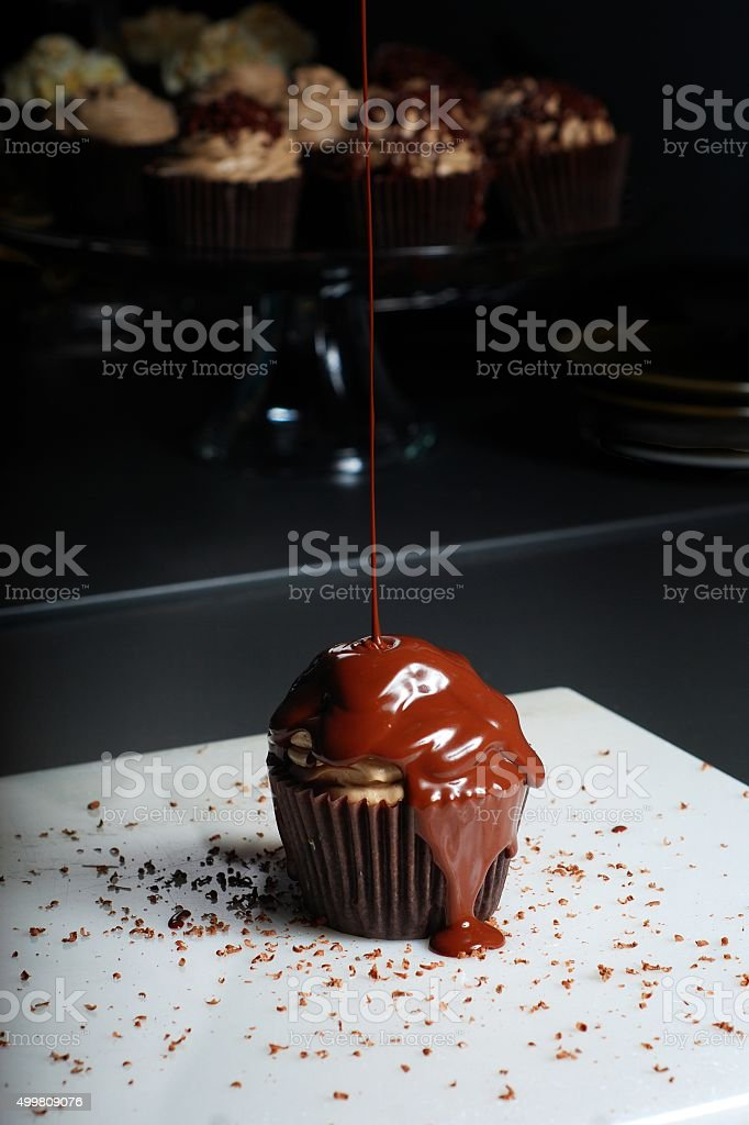 Chocolate cupcake drizzled with chocolate sauce stock photo
