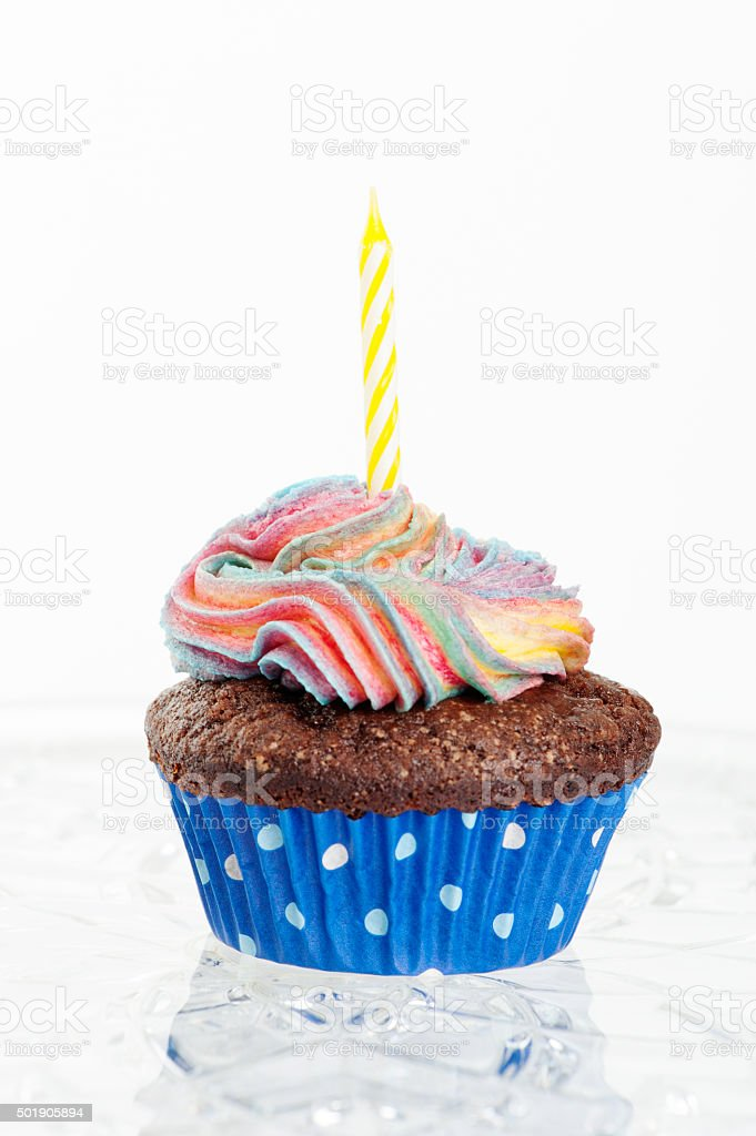 Chocolate cupcake with rainbow icing and a yellow candle stock photo