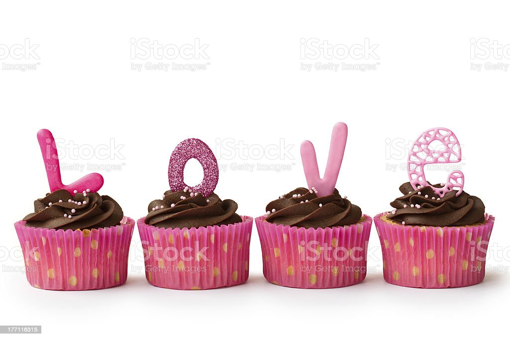 Chocolate cupcakes in pink wrappers with L-O-V-E letters royalty-free stock photo