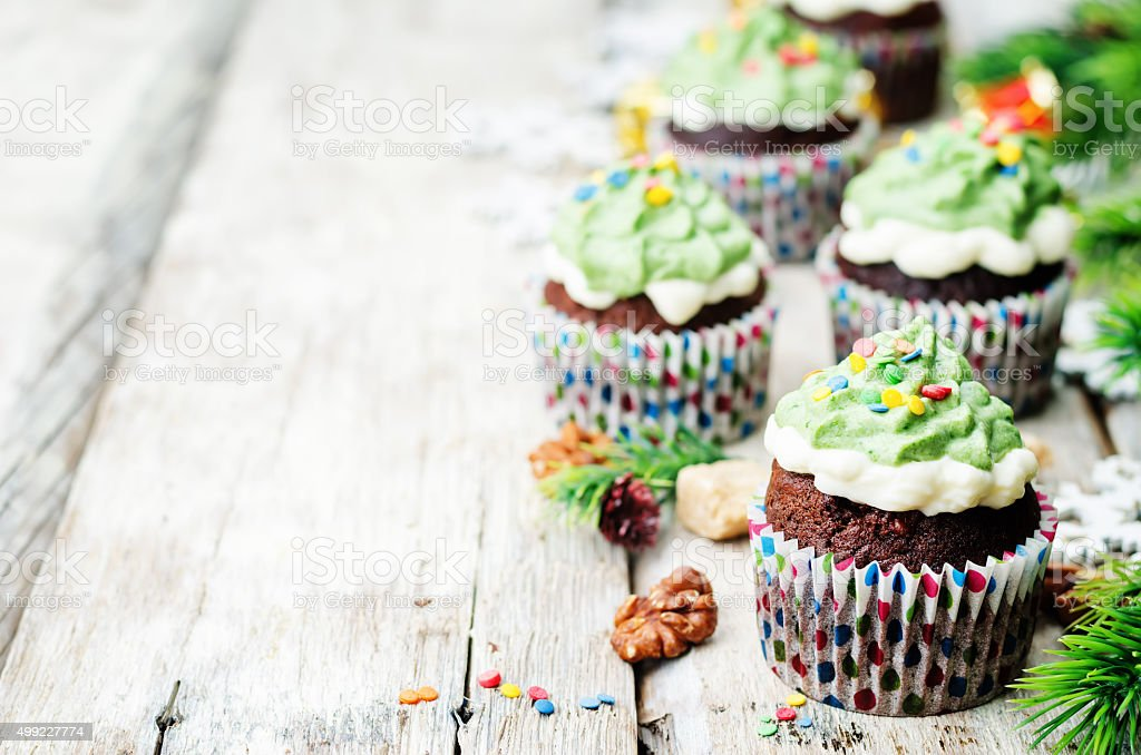 Chocolate cupcakes with green frosting and sprinkles on holiday stock photo