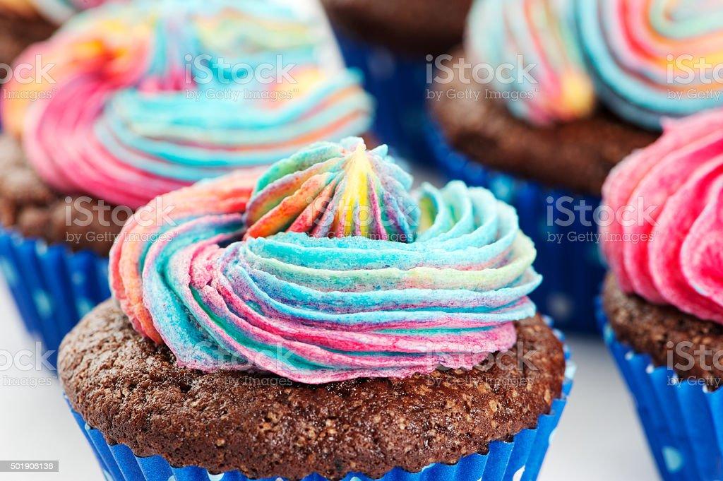 Chocolate cupcakes with rainbow icing stock photo
