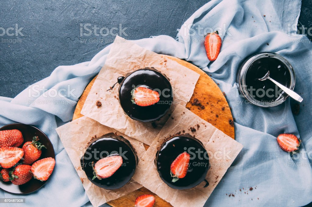 Chocolate cupcakes with strawberries on a dark background stock photo