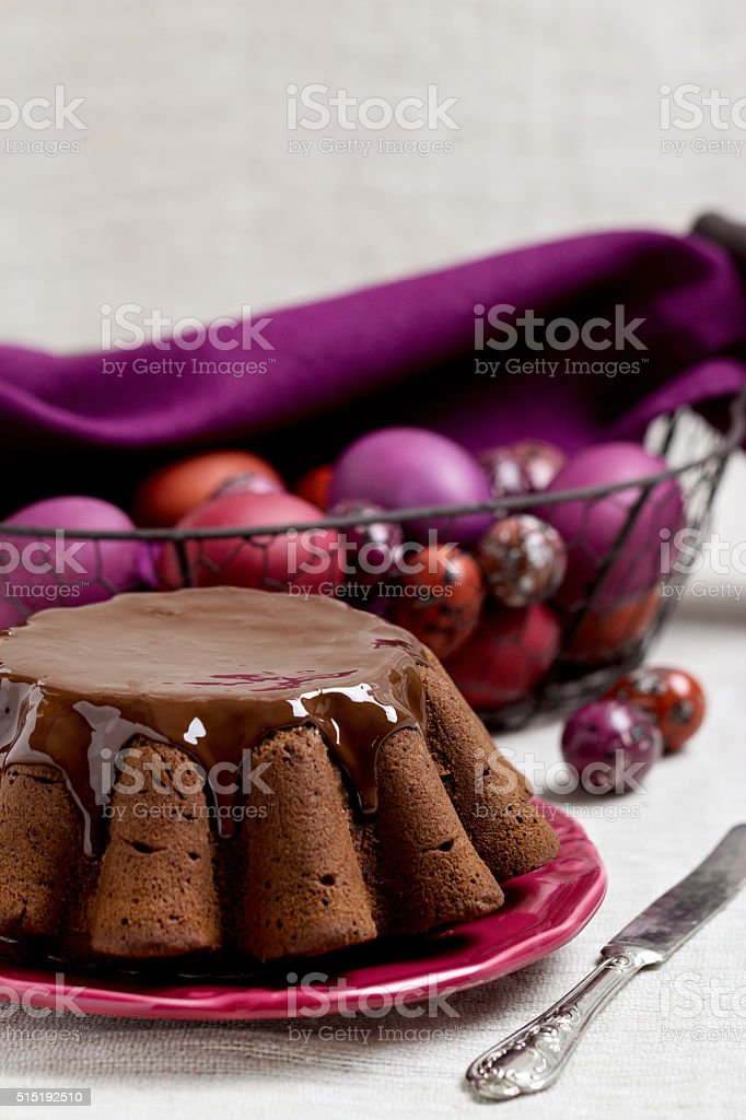 Chocolate Easter cake and Easter eggs colored in purple color stock photo