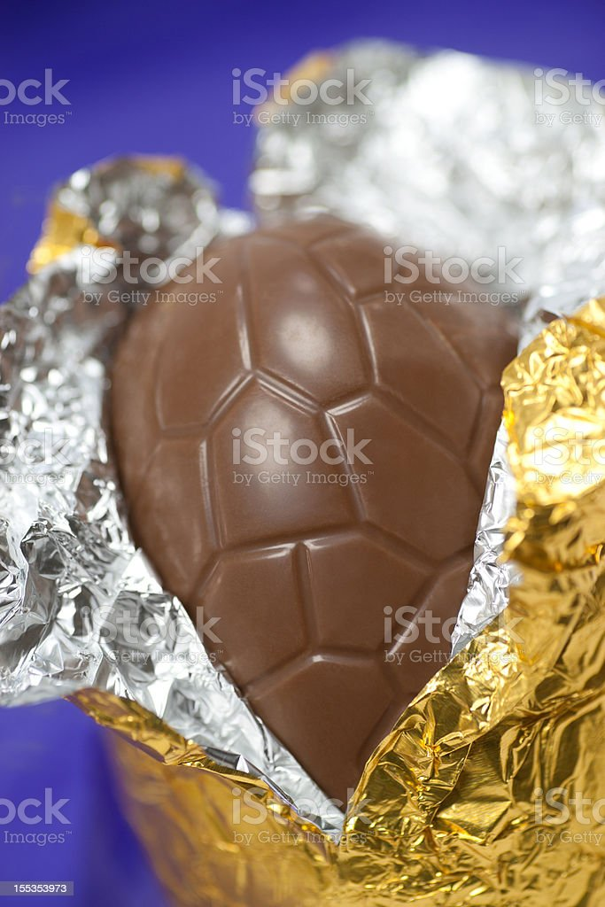 Chocolate easter egg in gold foil on purple stock photo
