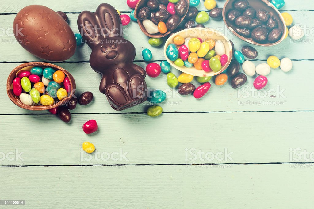Chocolate Easter eggs and rabbit , on wooden background stock photo
