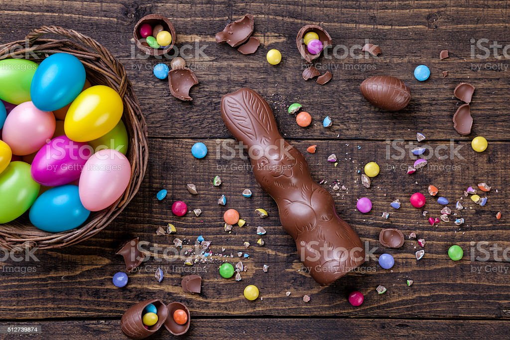 Chocolate easter eggs and sweets on wooden background stock photo