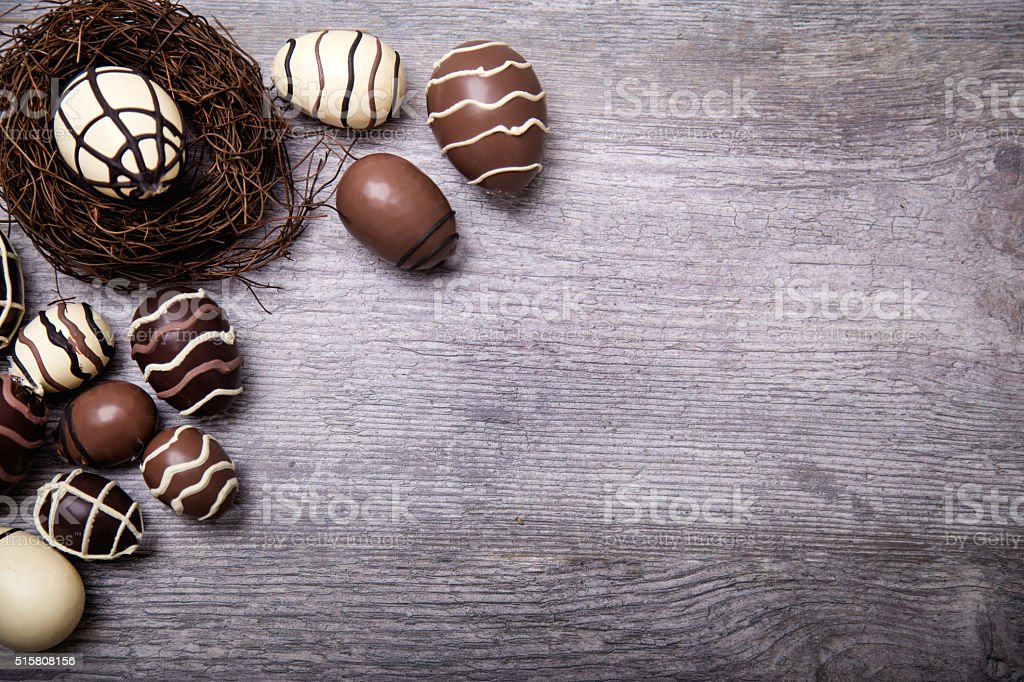 Chocolate Easter Eggs in nest Over Wooden Background stock photo