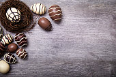 Chocolate Easter Eggs in nest Over Wooden Background