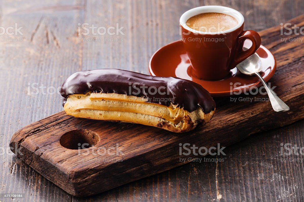 Chocolate eclair and coffee cup stock photo
