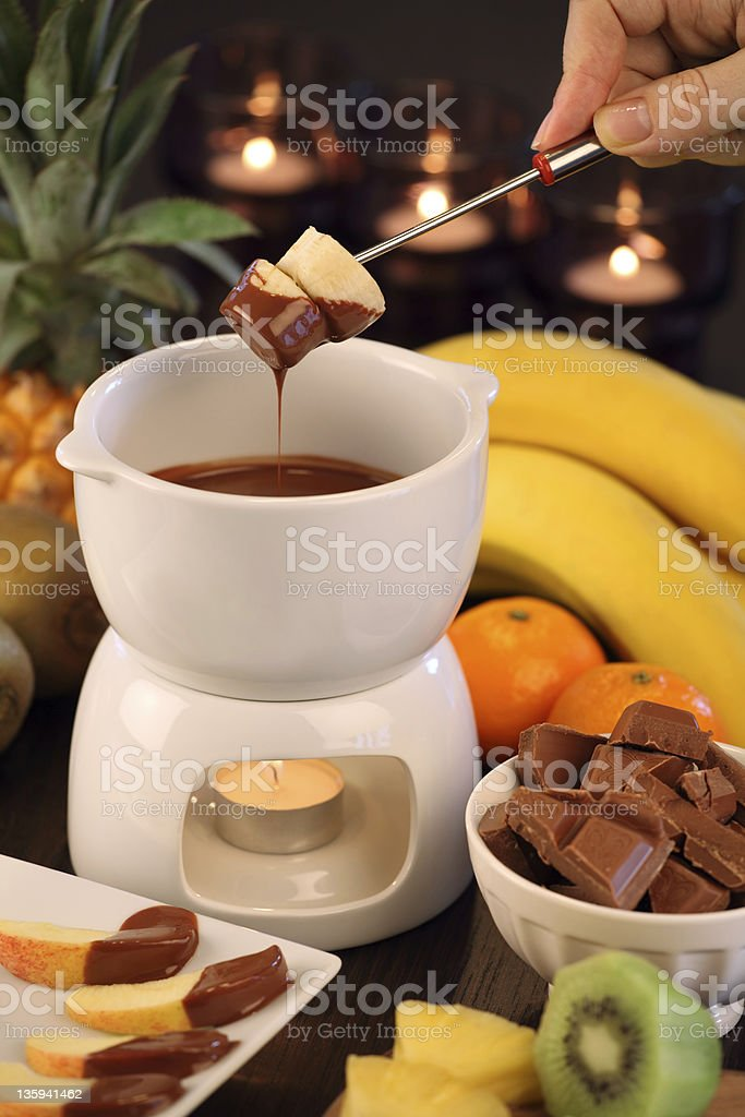 Chocolate fondue cup with candles and assorted fruits royalty-free stock photo