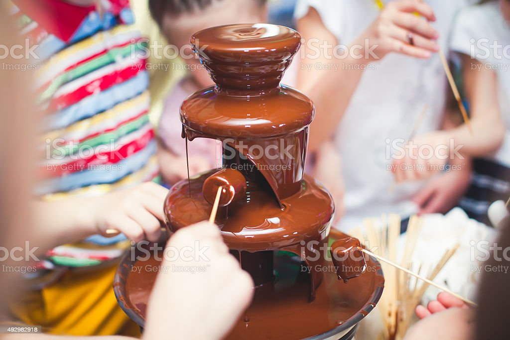 Chocolate Fountain With Fondue, Fruits and Marshmallow on children party stock photo