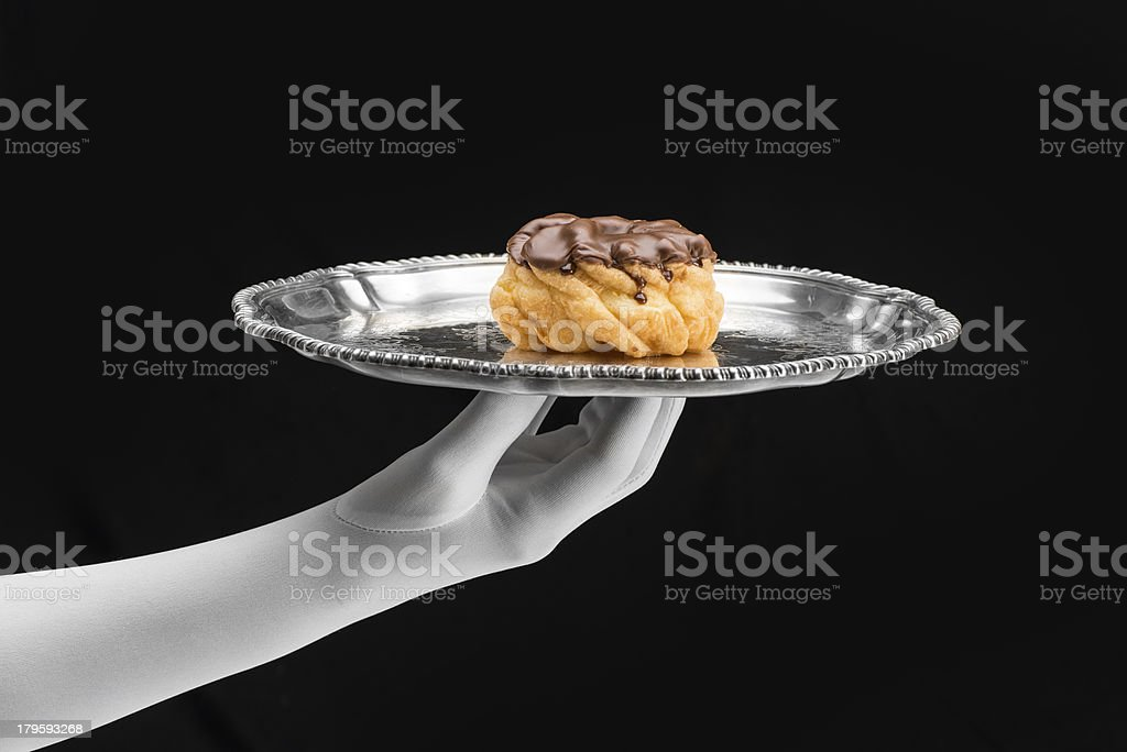 Chocolate frosted donut served on silver tray w/white gloved hand royalty-free stock photo