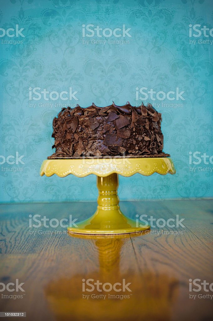 Chocolate gateau on a yellow cake stand on wooden table stock photo