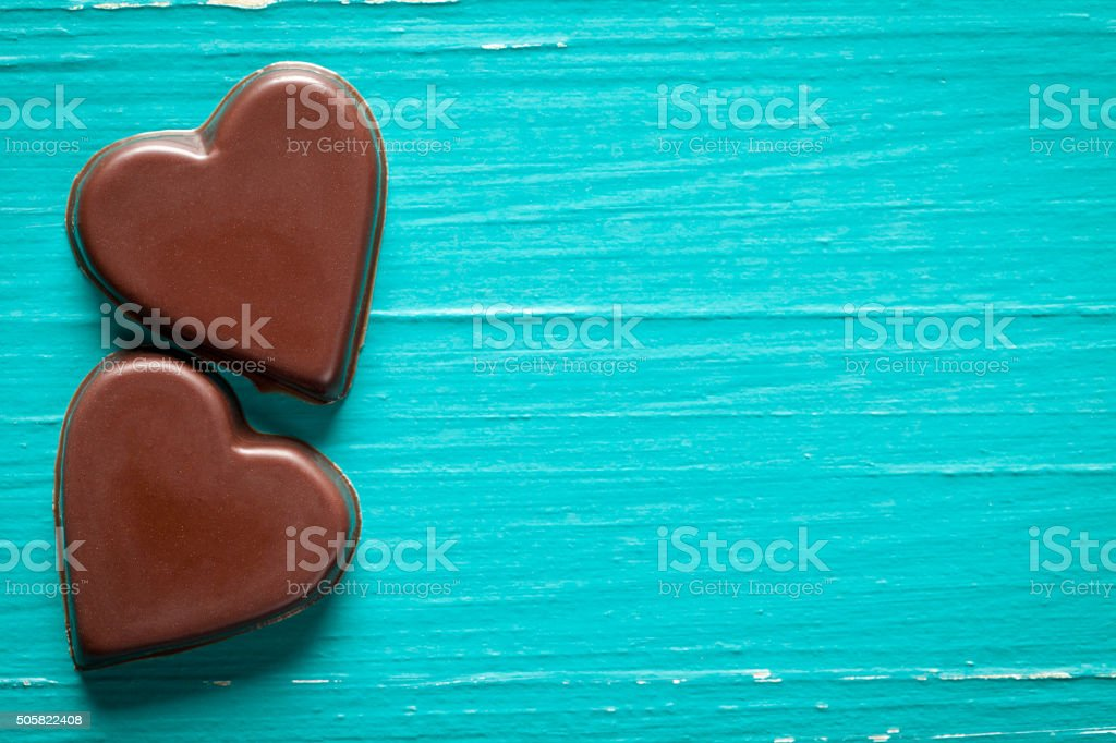 Chocolate hearts on old turquoise table stock photo
