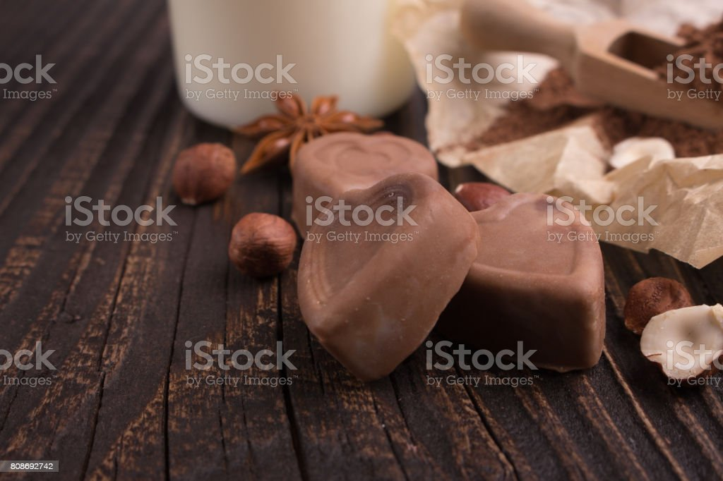 Chocolate heart-shaped candy on a rustic background, chocolate composition stock photo