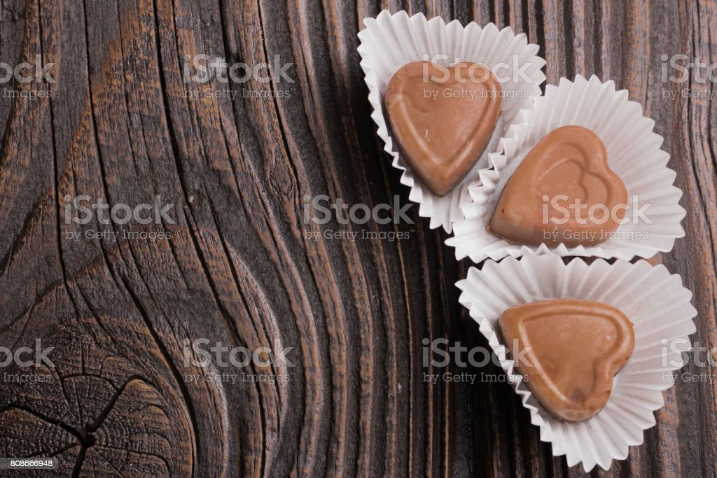 Chocolate heart-shaped candy on wooden background stock photo