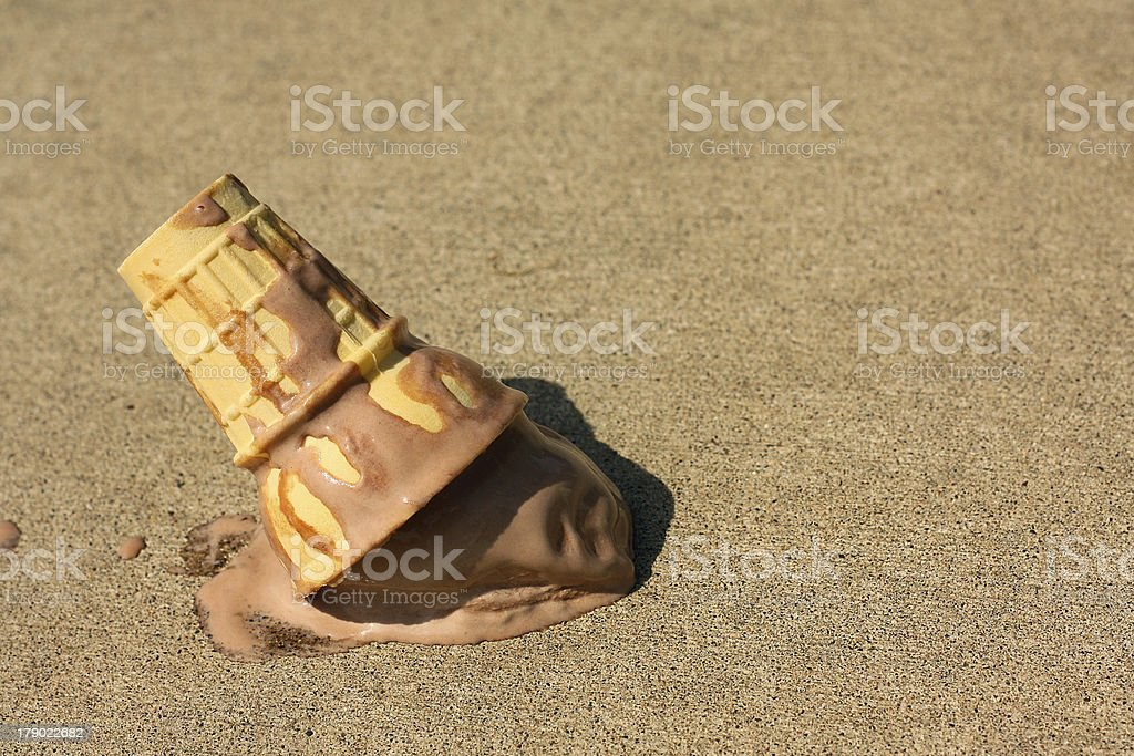 A chocolate ice cream cone melting on the ground stock photo